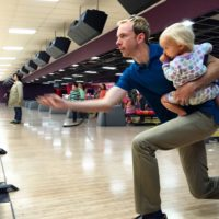 Ted Hawkes bowling with baby